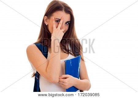 cheerful smart student girl in brown sport clothes with backpack on her shoulders and folder for notebooks in hands smiling and looking at the camera isolated on white.