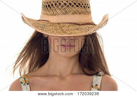 close up portrait without eyes of beautiful young brunette woman with straw hat posing isolated on white