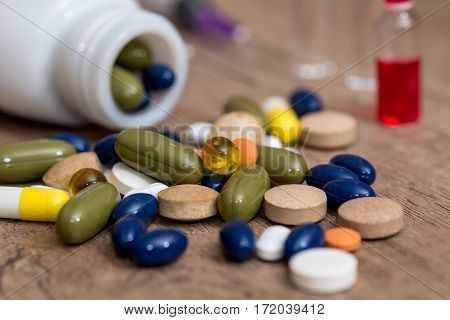 pills and syringe on desk close up