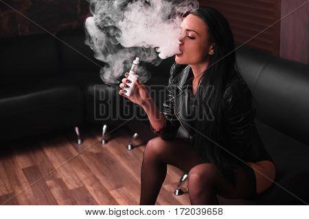 sexy brunette woman vaping electronic cigarette, vaponizer concept