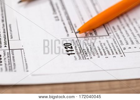 US 1120 tax form with pen close up
