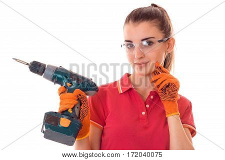 portrait of young charming brunette building woman in red uniform with drill in hands makes renovation and smiling on camera isolated on white