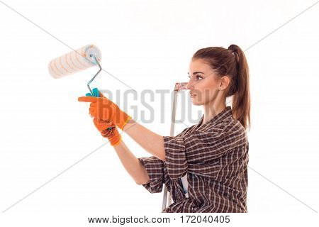 portrait of young concentrated brunette building woman with paint roller in hands makes renovation isolated on white