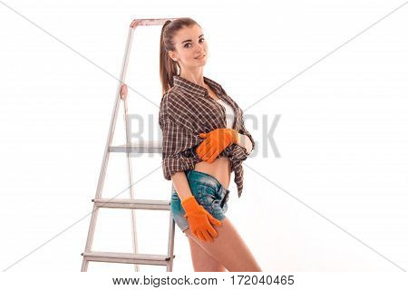 portrait of young sexual brunette building woman with ladder makes renovation and posing on camera isolated on white