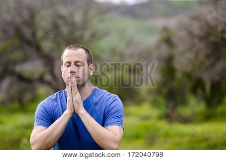 Man praying alone in nature embracing God's creation.