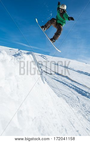 Snowboarder executing a radical jump against blue sky.