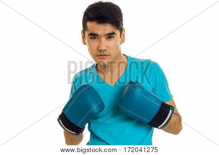 portrait of serious brunette sports man practicing box in blue gloves isolated on white