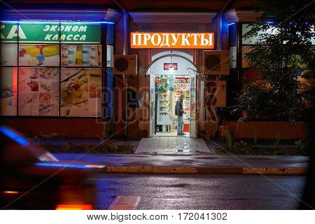 Moscow Russia - July 21 2015: Young man pays money in the food store at night on Eniseyskaya street. Russian texts are translated as food store in the center and pharmacy of economy level on the left.