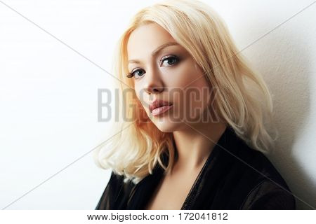 Fashion model posing in studio. Portrait of a beautiful blond woman with blue eyes