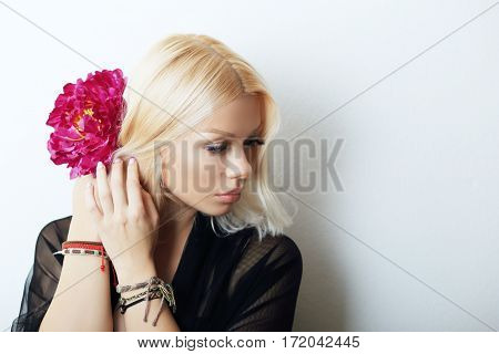 Fashion model posing with red flower. Portrait of a beautiful blond woman with blue eyes