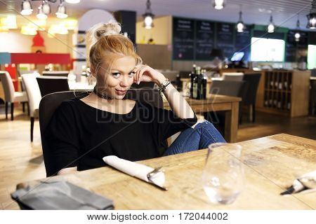 Charming woman in a restaurant smiling to camera