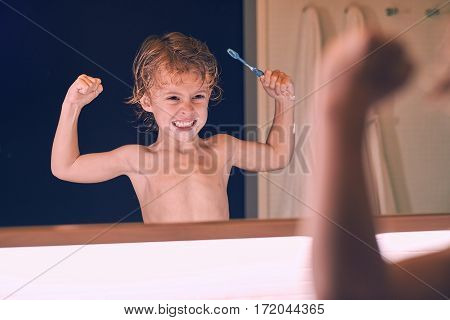 Child brushing itself the teeth in the bathroom