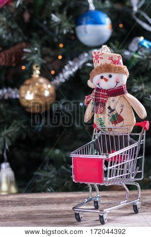 Happy Christmas snowman sitting in shopping cart
