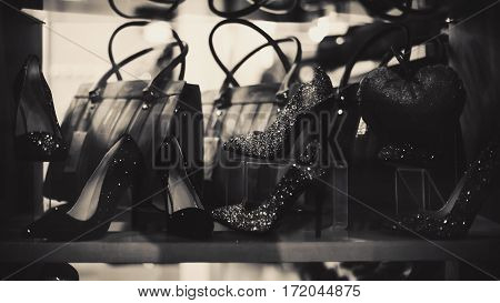 Closeup view on window of a shop for selling luxury woman shoes and bags.