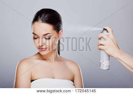 Beauty portrait of young girl with perfect nude make-up, closed eyes. Someone sprinkling hairspray on her hair. Beauty salon. Head and shoulders, studio, indoors