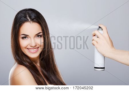Beauty portrait of young girl with perfect nude make-up. Someone sprinkling hairspray on her loose hair. Looking at camera and smiling. Beauty salon. Head and shoulders, studio, indoors