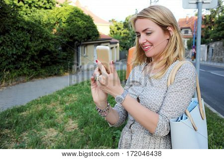 smiling attractive female shooting something on her mobile phone