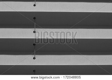 Window gray pleated blind close up with details in home interior. Structure and texture of fabric background.