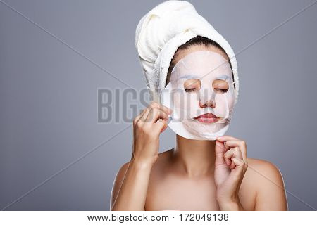Girl rending white mask. Model pulling away mask from her face. Closed eyes. Head and shoulders, studio, indoors