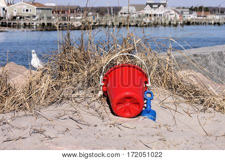 Child's toy plastic pail and shovel leaning against dry sea grass on the edge of a rock jetty.
