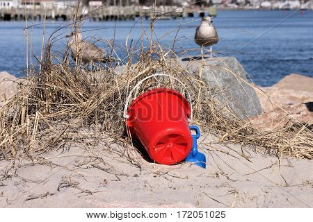 Child's plastic pail and shovel leaning on dried sea grass along side of a harbor jetty.