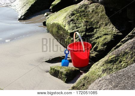 Red pail and blue shovel sitting among the jetty rocks at low tide.