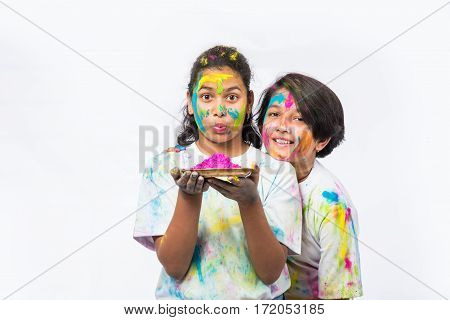 two indian girls celebrating holi with gulal in thali, isolated over white background