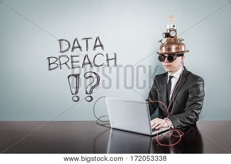 Data breach text with vintage businessman using laptop at office
