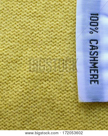 Cashmere texture.Cashmere background.100% Cashmere wool texture.Fabric label on yellow cashmere background.
