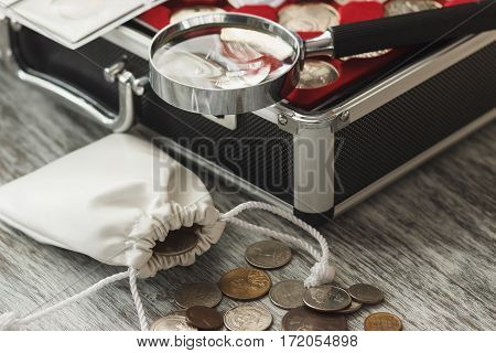 Different Collector's Coins With A Magnifying Glass And Money Bag