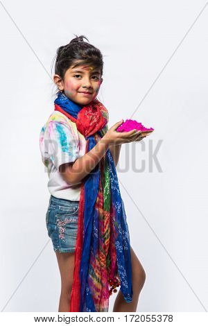 one indian girls celebrating holi with gulal in thali, presenting something, isolated over white background