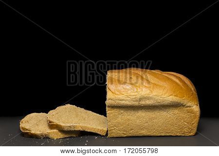 A partially sliced loaf of honey wheat bread.
