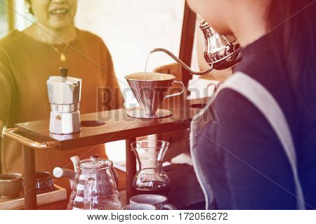 Young woman barista talking with customer