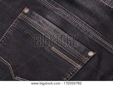 back pocket of dark jeans close up.