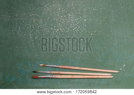 Paint brushes paint on a green shabby background