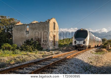 Train passing a derelict station at Lumio in the Balagne region of Corsica with snow covered mountains in the distance under a deep blue sky