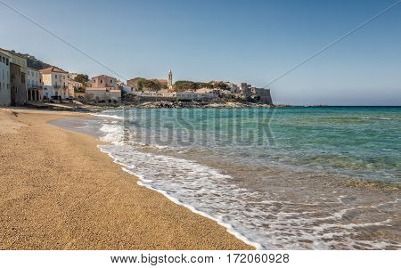 Turqouise Mediterranean sea lapping gently onto the golden sandy beach in front of the Balagne village of Algajola in Corsica