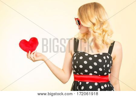 Woman blonde lovely girl wearing dotted dress sunglasses holding red heart love symbol studio shot on bright. Valentines day happiness concept