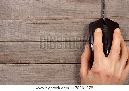black computer mouse with a hand on old wooden background with copy space for your text. Top view.