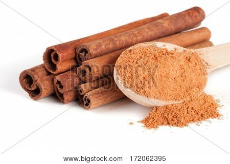 a stack of cinnamon sticks and powder with spoon isolated on white background.