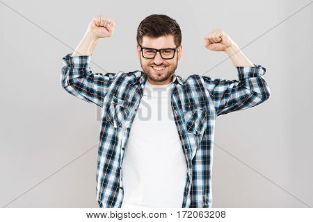 Man in checked T-shirt and eyeglasses with hands up. Looking at camera, clenched fists, smiling. Indoors, studio, waist up