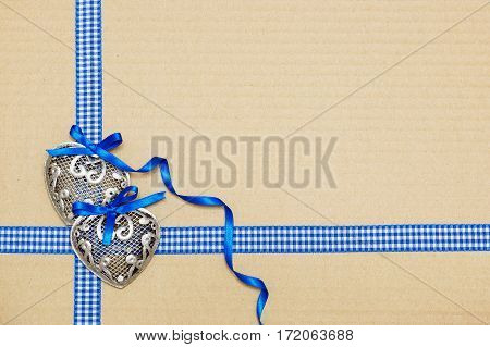 Valentine's Day card. Two silver hearts on a cardboard box.