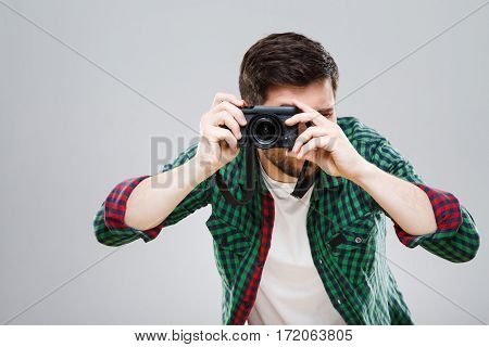 Man in green checked T-shirt holding camera making photos. Young man, casual style. Photographer. Indoors, studio, waist up