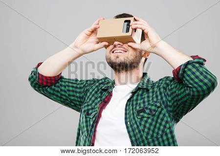 Man in green checked T-shirt looking at vr box, Virtual Reality Glasses, cardbox. Waist up. Indoors, studio