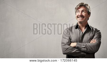 Handsome smiling casual man over gray wall background.