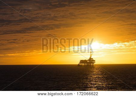 Off shore oil rig silhouetted by a bright yellow sunset