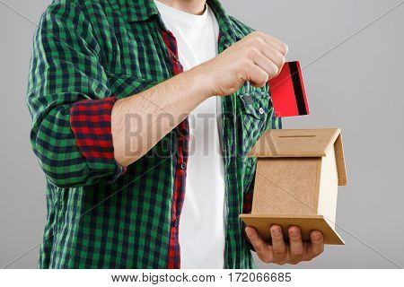 Man in green checked T-shirt holding little wooden house, mini model of house. Throwing red credit card into money box. Close up, without head. Indoors, studio
