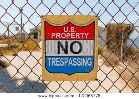 US property no Trespassing sign hung on chain link fence