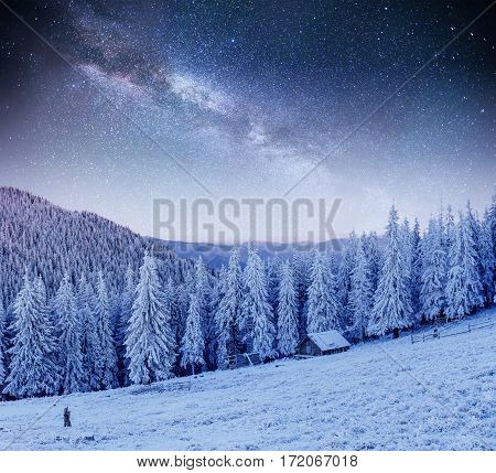 chalets in the mountains at night under the stars. Magic event in frosty day. In anticipation of the holiday. Dramatic scenes. Carpathians, Ukraine, Europe