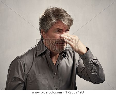 Man hiding his nose bad smell over gray background.